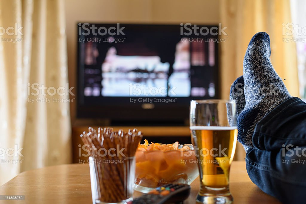TV watching (movie) with feet on table and snacks stock photo