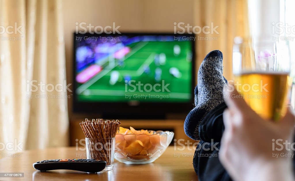 TV watching (football match) with feet on table and snacks stock photo