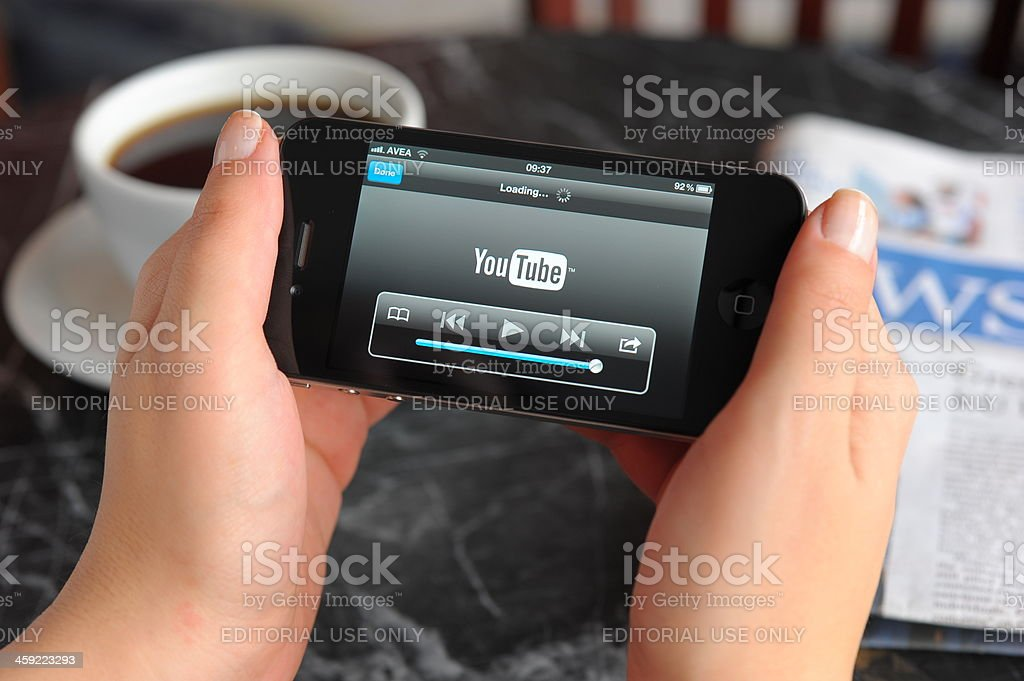 Watching Youtube video with iPhone 4 stock photo