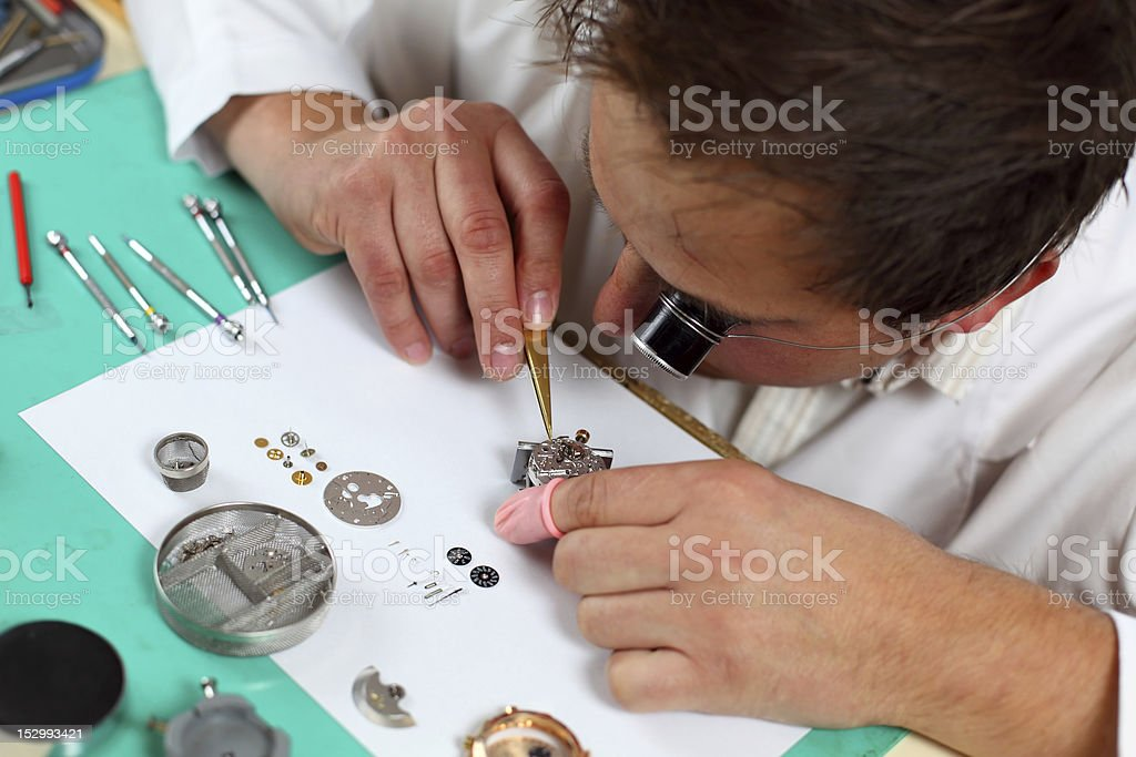 Watchmaker assembling watch with microscopic eye device stock photo