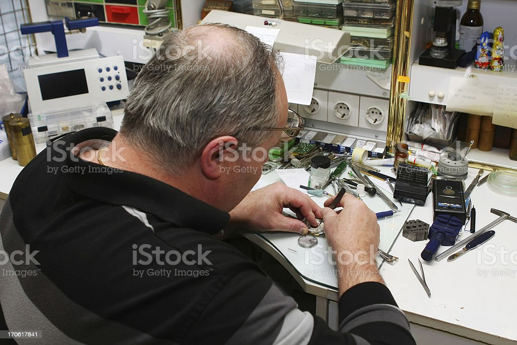 Watchmaker in his office...repairing wrist watch,chaos on the table royalty-free stock photo
