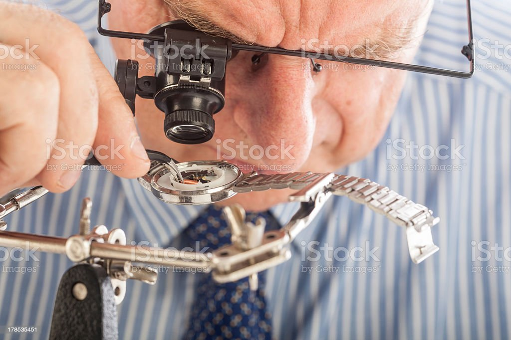 Watchmaker looking closely at inside of silver watch face stock photo