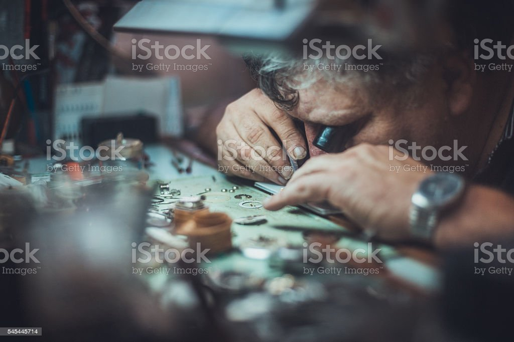 watchmaker looking through monocle at watch stock photo