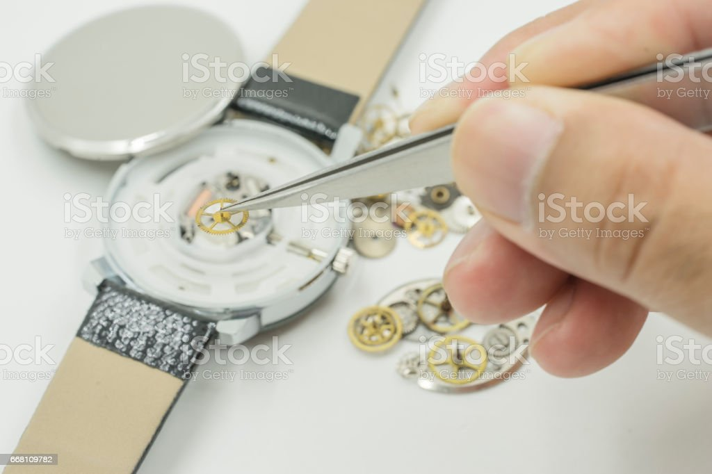 watchmaker select small yellow gear from watch stock photo