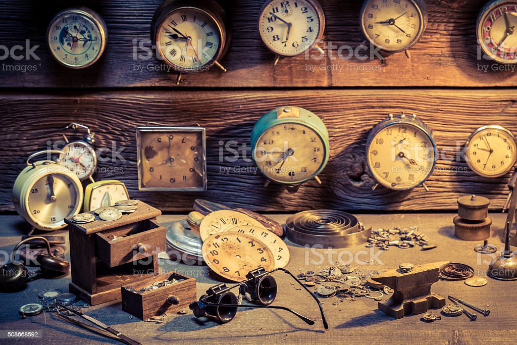 Watchmaker's workshop with parts of clocks stock photo