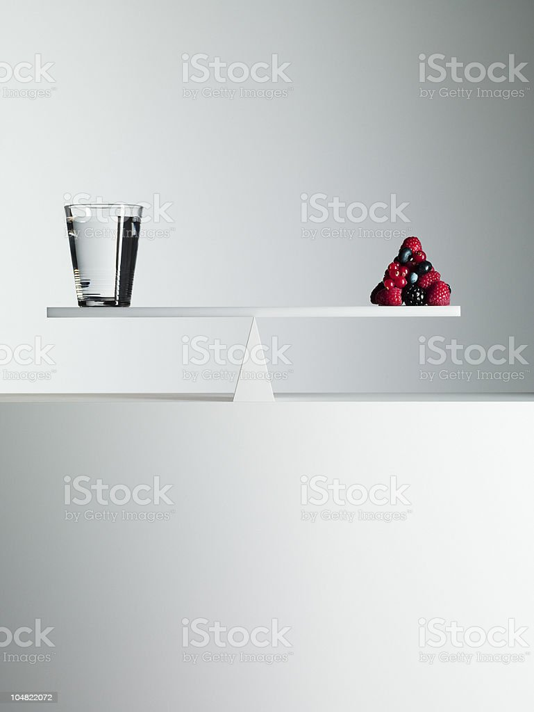 Water and berries balanced on opposite ends of seesaw royalty-free stock photo