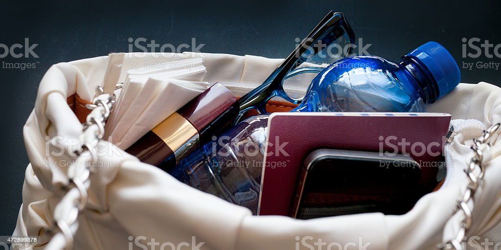 Water and Essentials in a small fashion pouch stock photo