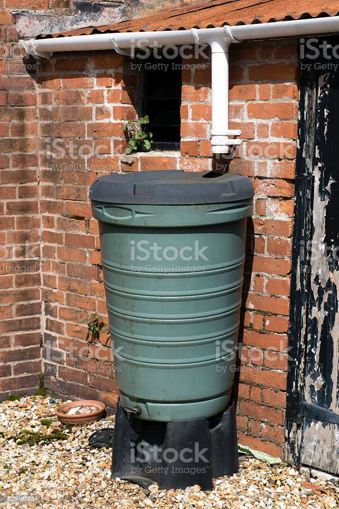 Water barrel fed by guttering from a rusty shed roof stock photo