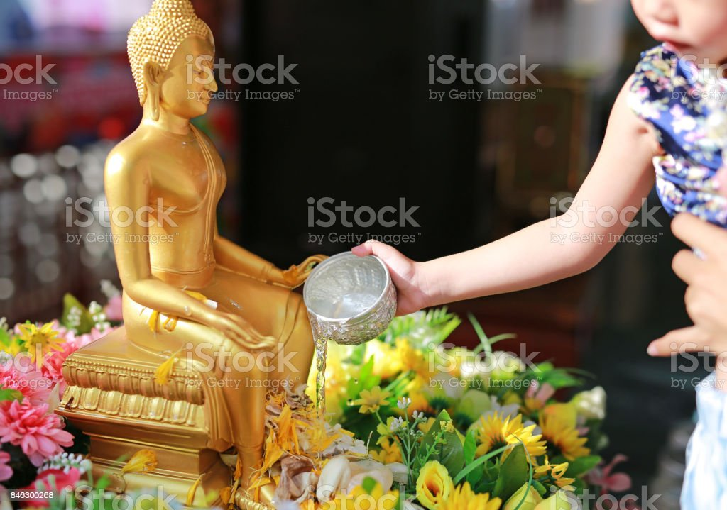 Water blessing ceremony for Songkran Festival or Thai New Year. Child girl paying respects to a statue of Buddha by pouring water onto it. stock photo
