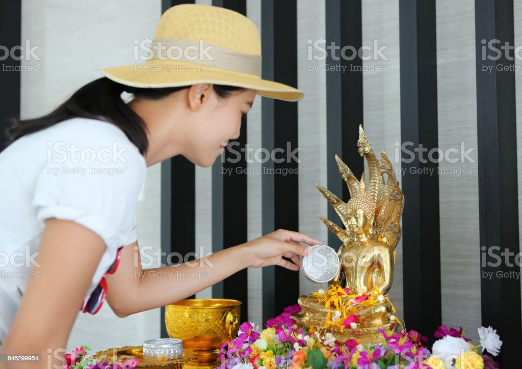 Water blessing ceremony for Songkran Festival or Thai New Year. Women paying respects to a statue of Buddha by pouring water onto it. stock photo