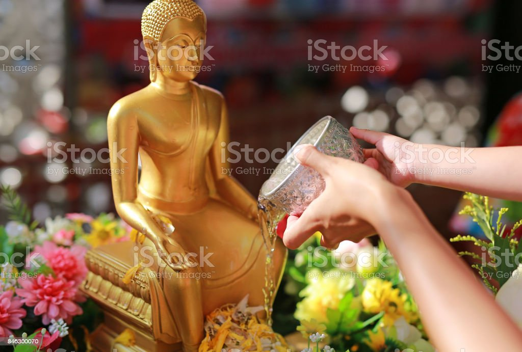 Water blessing ceremony for Songkran Festival or Thai New Year. Women and child girl paying respects to a statue of Buddha by pouring water onto it. stock photo