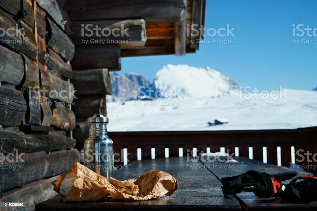 water bottle and sandwich on wooden table in winter landscape stock photo