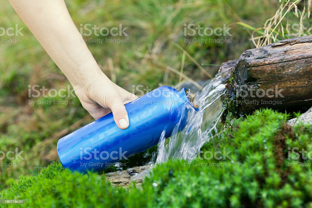 Water bottle and stream on hike royalty-free stock photo