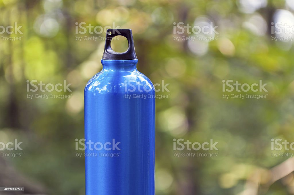 Water bottle in green forest stock photo