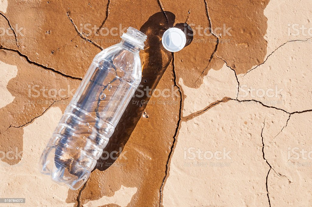 Water bottle on dry ground stock photo