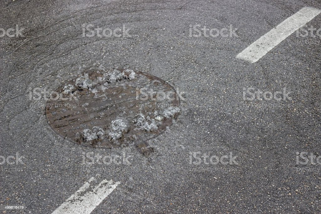 Water bubbling up through manhole cover and sewer stock photo