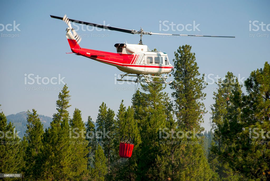Water bucket carried by helicopter to a fire stock photo