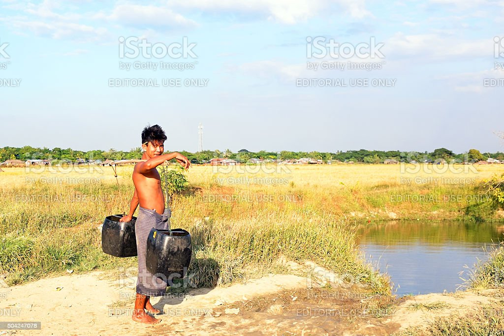Water carrier with two buckets in the countryside from Myanmar stock photo