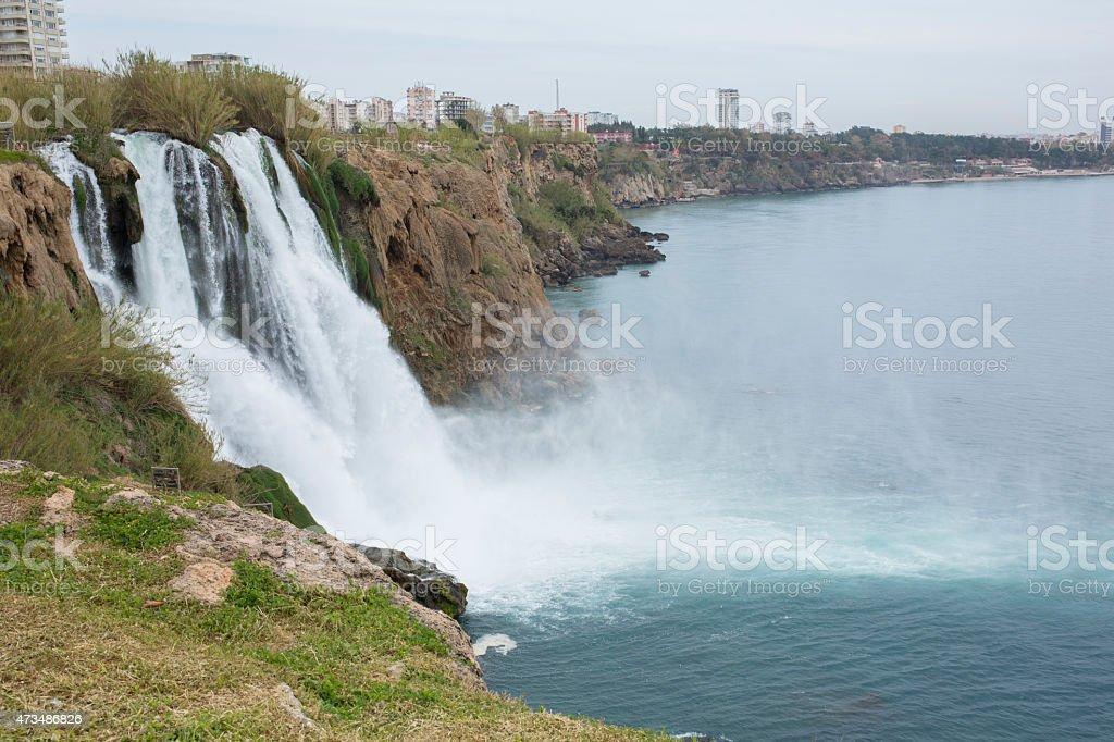 Water cascades from urban waterfall, sea below stock photo