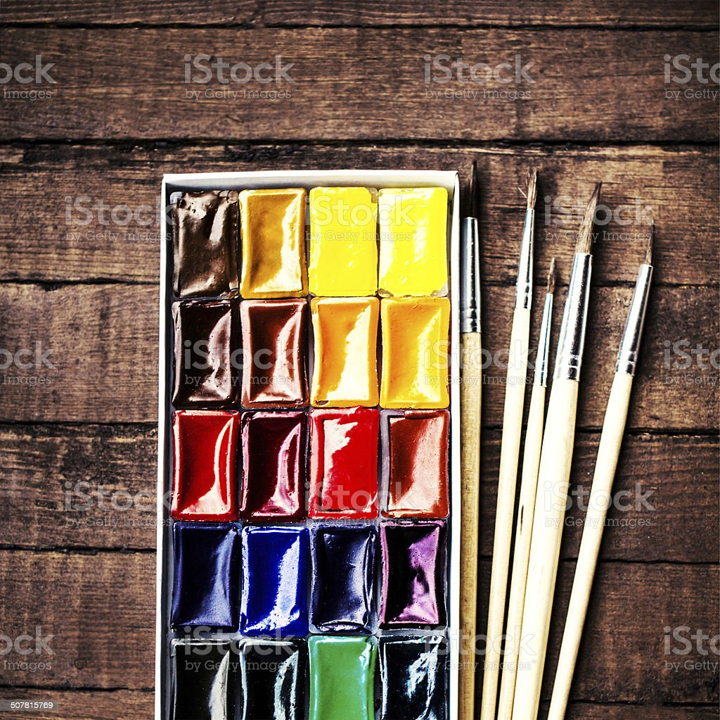 Water color drawing, paints and brushes over vintage wooden back stock photo