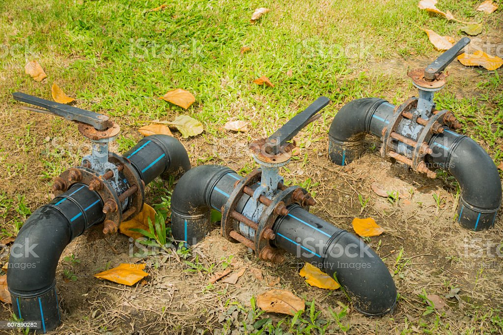Water control valve on field grass, HDPE pipeline. stock photo