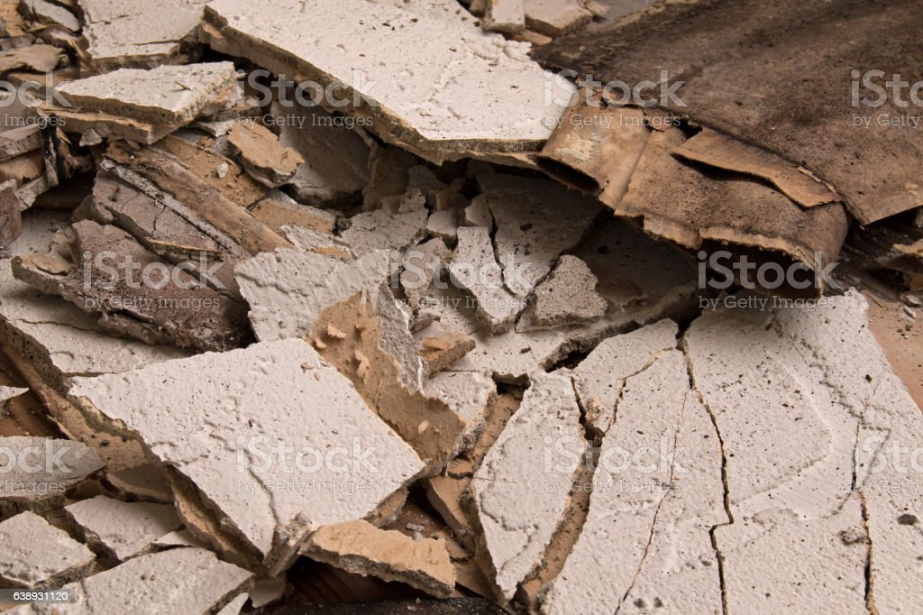 Fallen pieces of broken stucco caused by water damage.