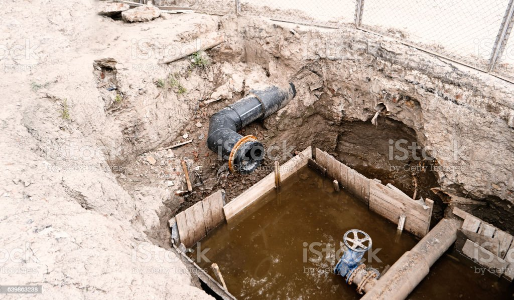Water Delivering PVC Plastic Pipes in Ground Hole during Plumbing stock photo