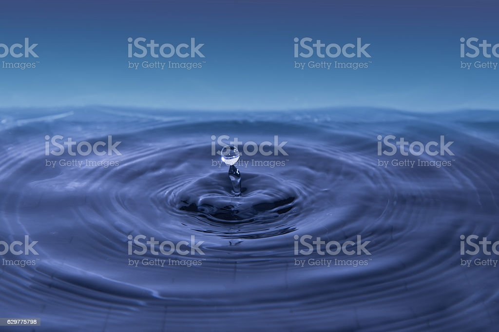 Water drop falling into water making a concentric circles stock photo