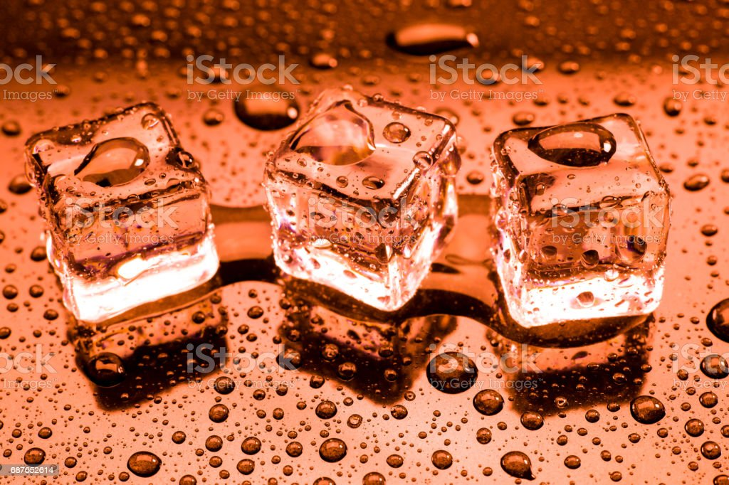 Water drop with ice cubes on lighting red background. stock photo