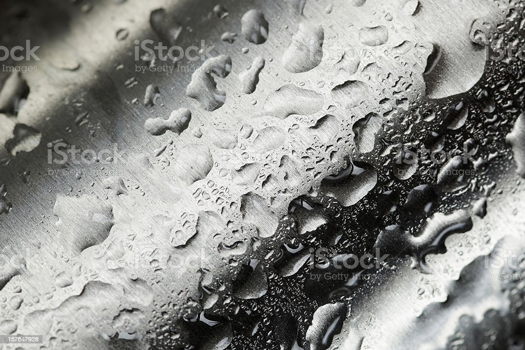 Water droplets collecting on waved metal stock photo