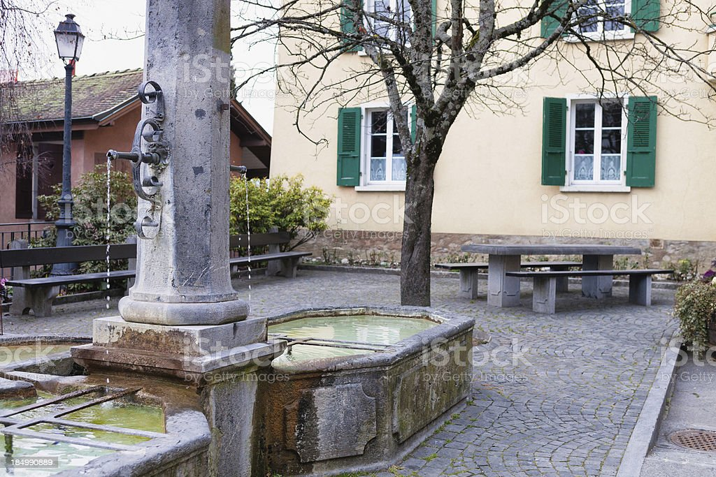 Water drops from fountain in a village Square stock photo