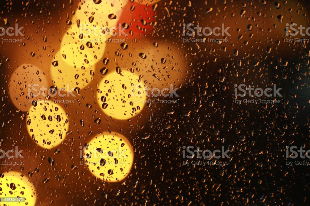 Water drops on window glass. Night city views de-focus. stock photo