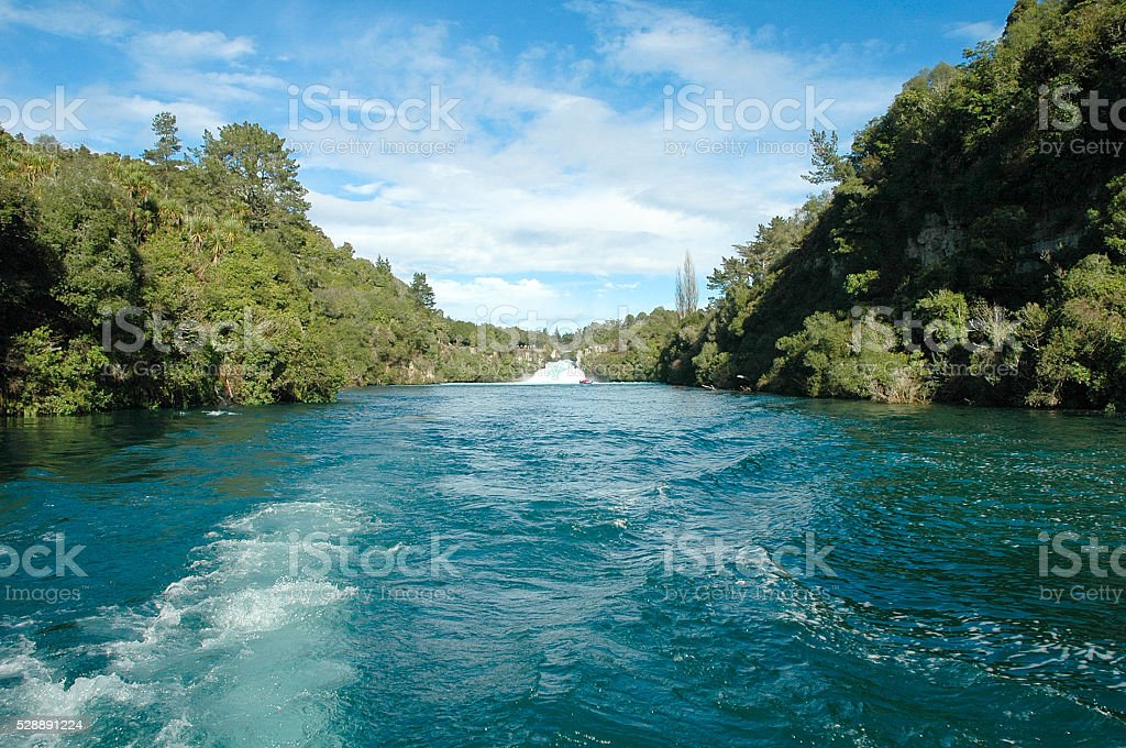 Water falls against a green forest and blue skies stock photo