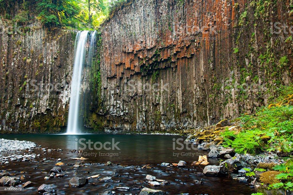Water falls over cliff of columnar basalt stock photo