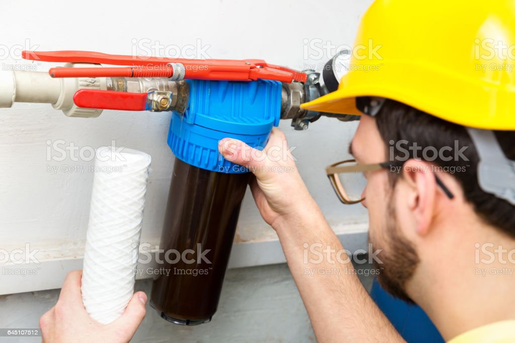 water filtration - plumber changing dirty water filter stock photo