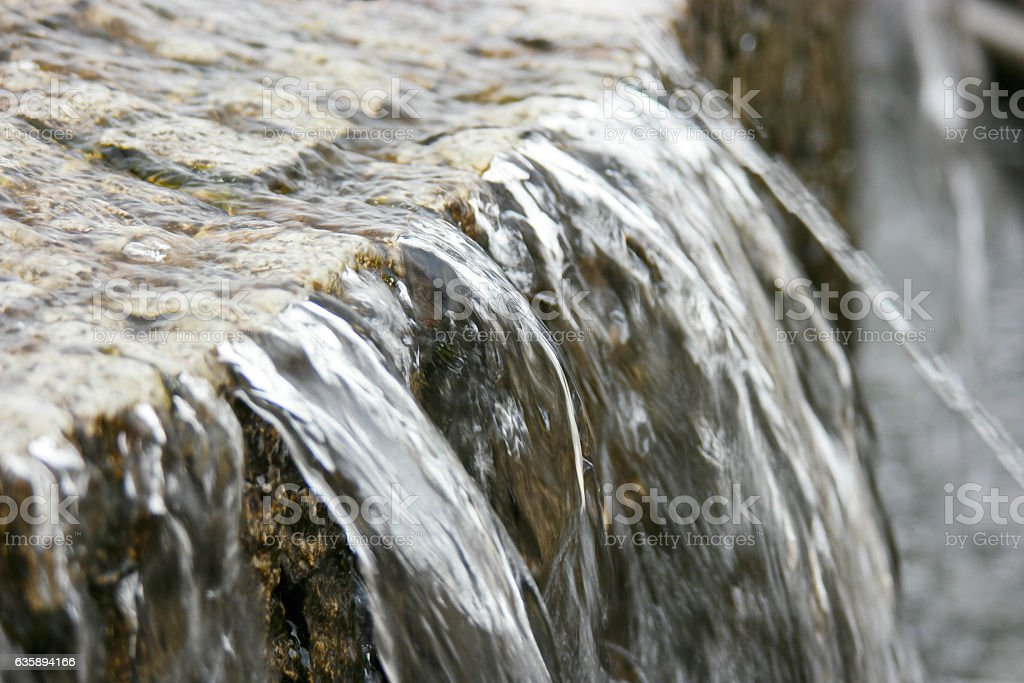 Water flow over stone edge of old city fountain stock photo