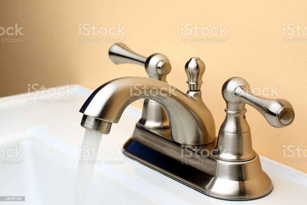 Water flowing from Brushed Nickel Faucet on Porcelain Bathroom Sink stock photo