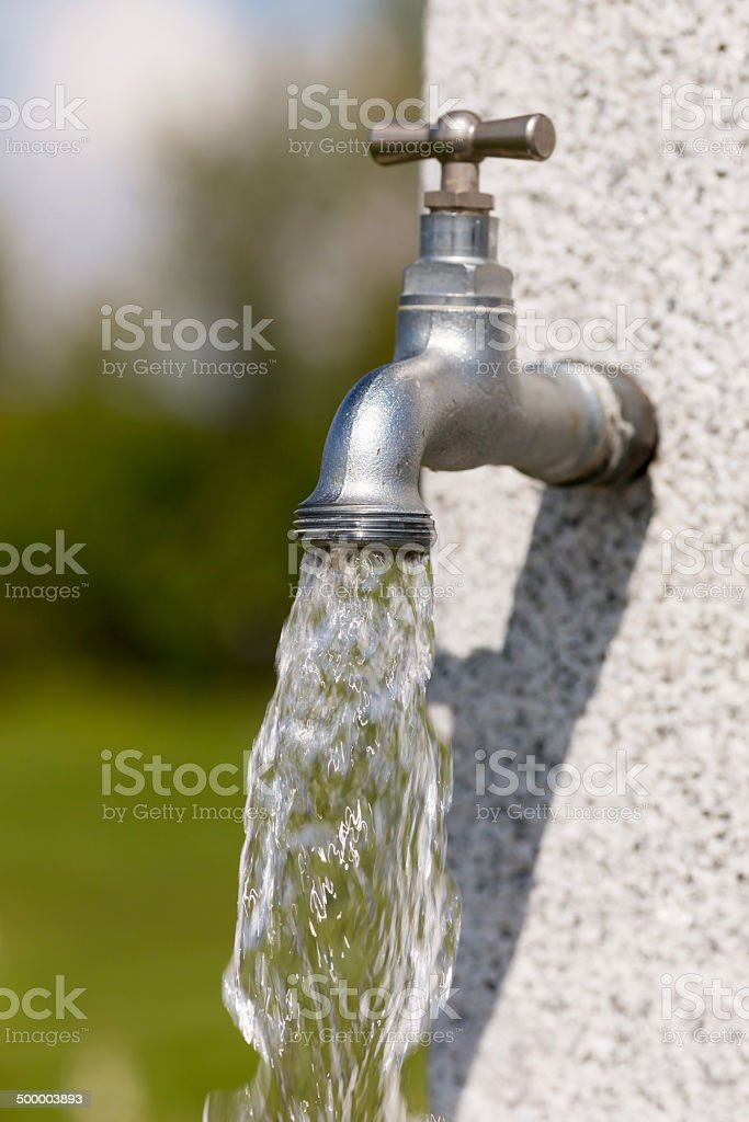 Water flowing from faucet stock photo