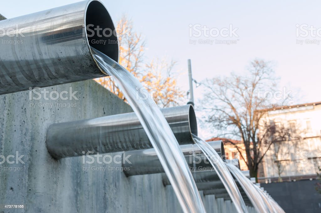 Water flowing from steel pipes in a line stock photo