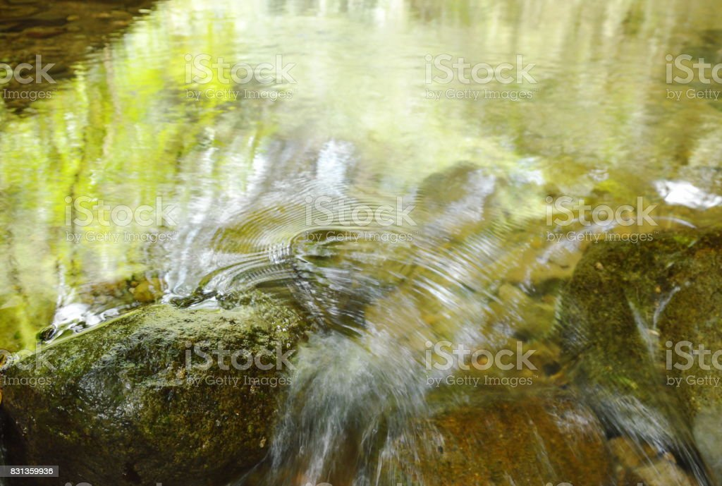 water flowing hit the rock and wave splashing stock photo