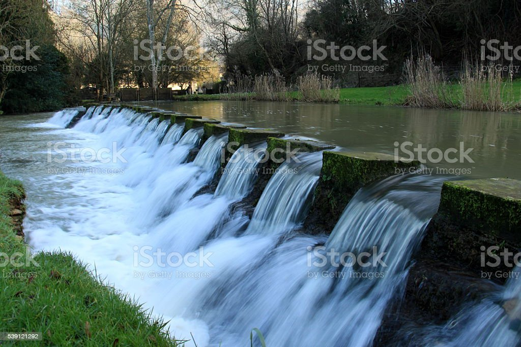 Water flowing in a Weir in the Countryside stock photo