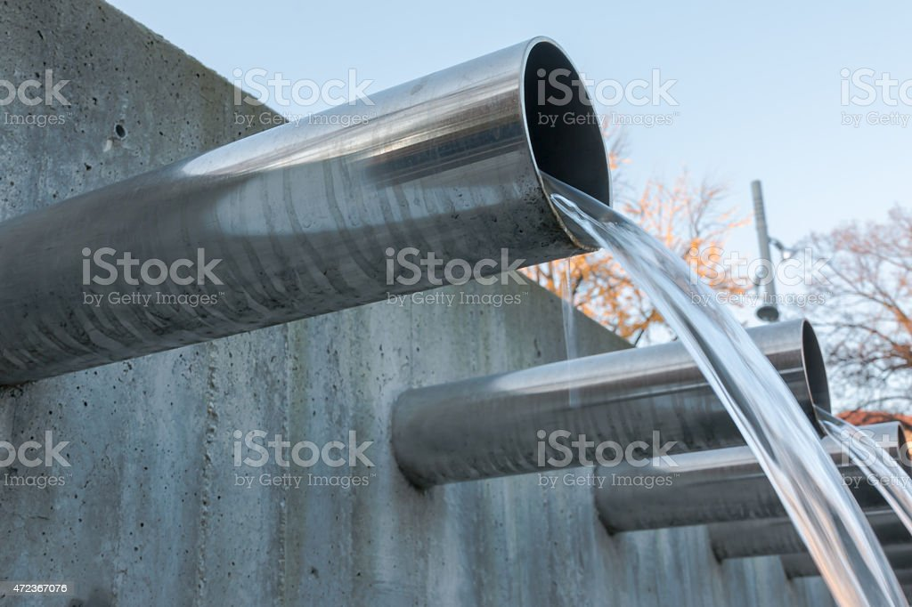 Water flowing out from steel pipes stock photo
