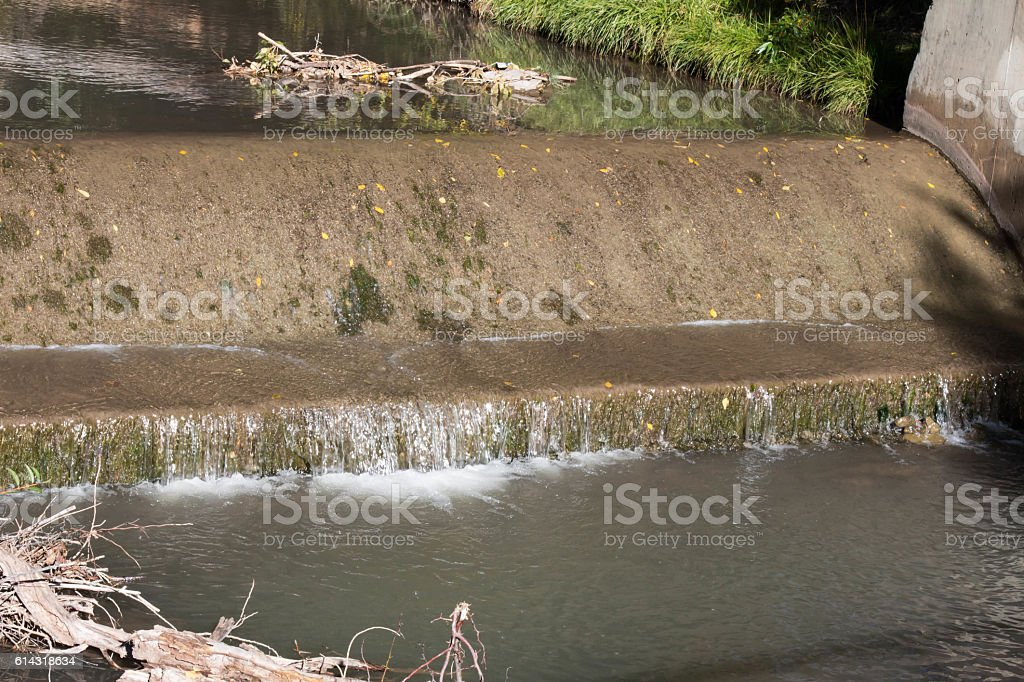 Water flowing over a small concrete weir stock photo