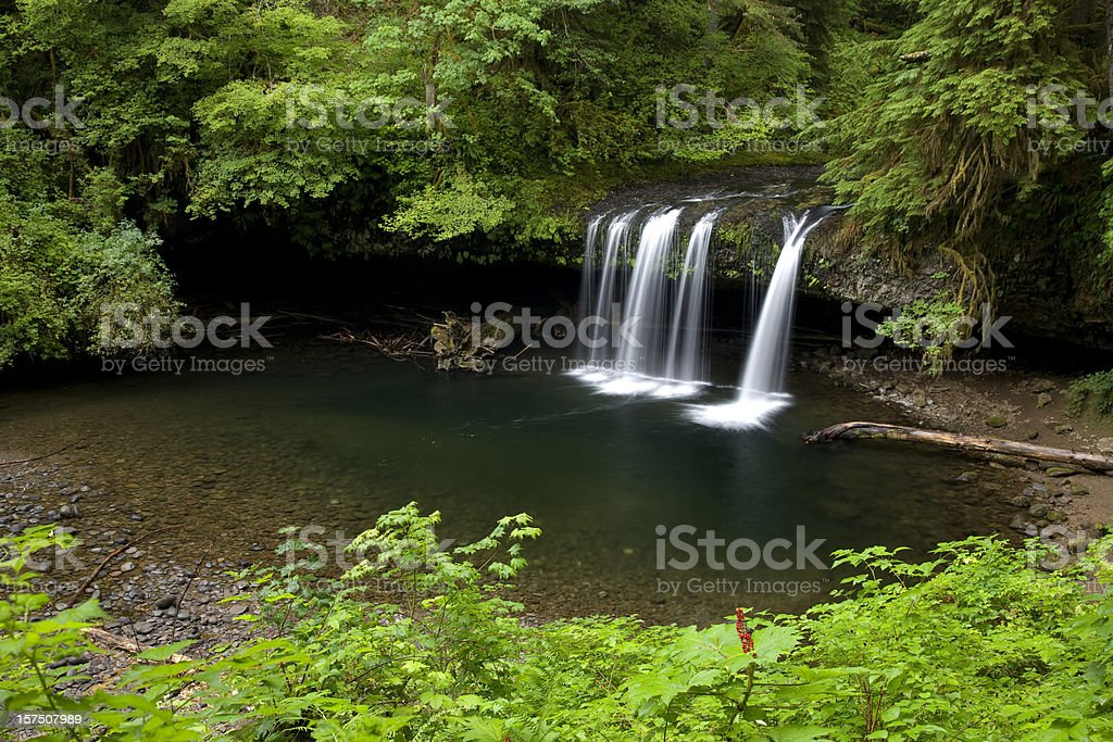 Water flowing over columnar basalt outcropping into pool stock photo