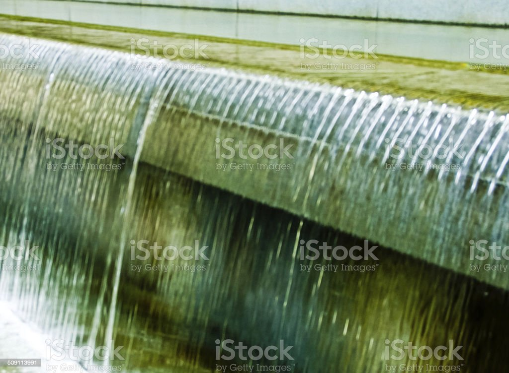 Water flowing over edge of granite wall into a pool stock photo