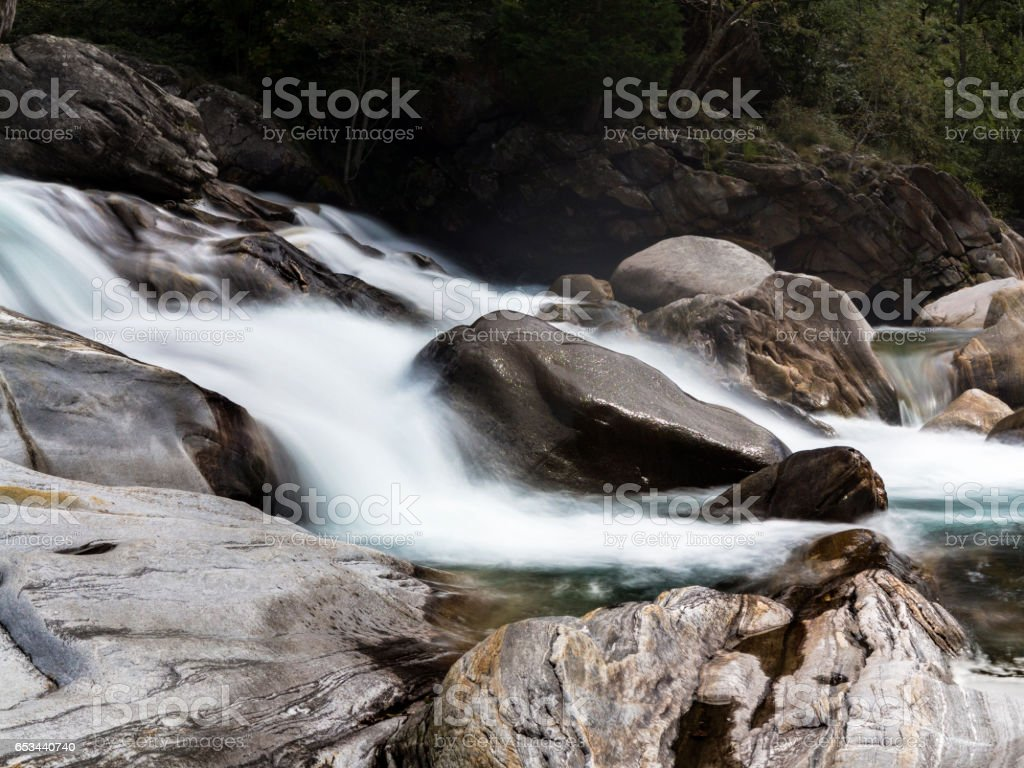 Water flowing over smooth stone stock photo