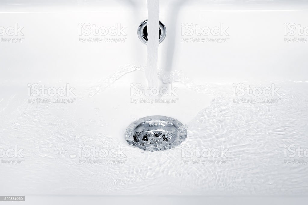 Water flowing, ripples and bubbles in sink stock photo