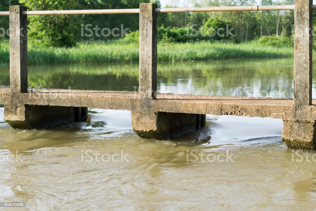 Water flows through the weir. stock photo