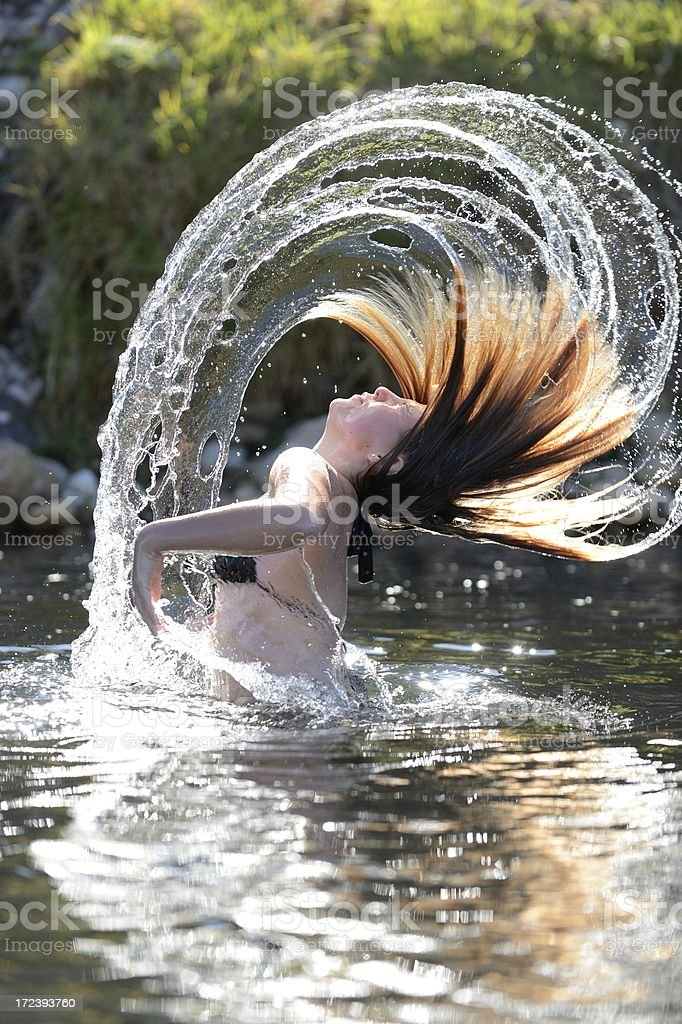 Water flying off young girl's hair vertical royalty-free stock photo