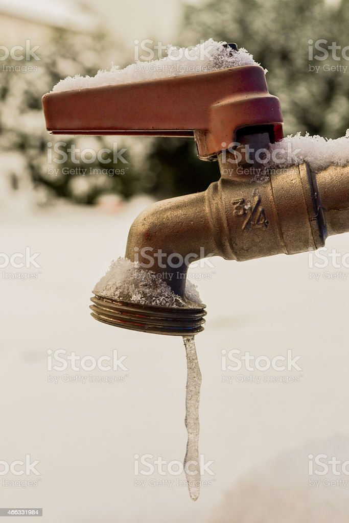 Water freezes as it leaves a tap stock photo
